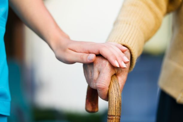 Image of an elderly person being guided by a younger person